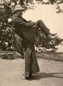 A British merchant being carried by a Sikkimese woman. West Bengal, ca. 1903.